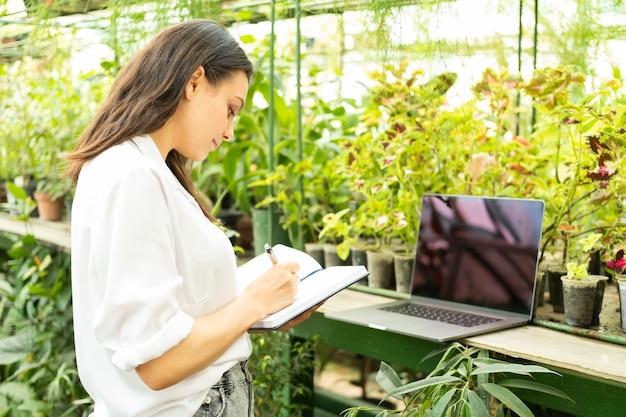 Jardineiro de mulheres de negócios jovem, escrevendo no caderno, usando o laptop em estufa. tecnologia moderna em jardinagem.