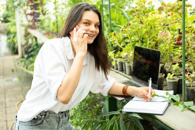 Jardineiro de mulheres de negócios jovem falando no telefone, escrevendo no caderno em estufa.