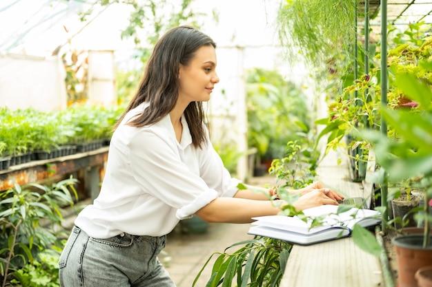 Jardineiro de mulheres de negócios jovem usando laptop em estufa. tecnologia moderna em jardinagem.