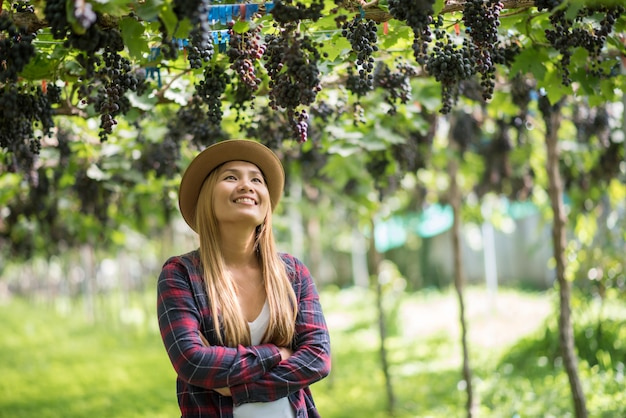 Jardineiro de mulheres jovens felizes segurando galhos de uva azul madura