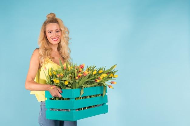 Jardineiro de uma linda mulher loira segurando uma caixa com tulipas na parede azul com espaço de cópia