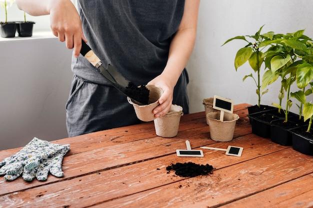 Jardineiro, derramando o solo em um vaso de flores