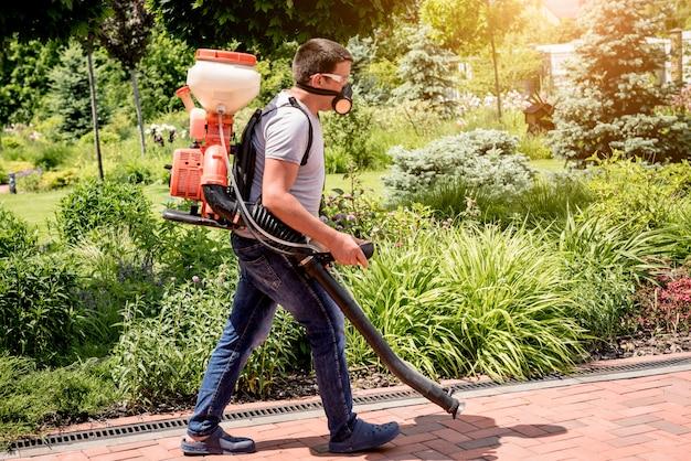 Jardineiro em máscara protetora e óculos de pulverização de árvores de pesticidas tóxicos