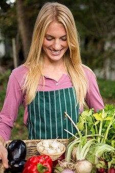 Jardineiro feliz com legumes frescos na cesta no jardim