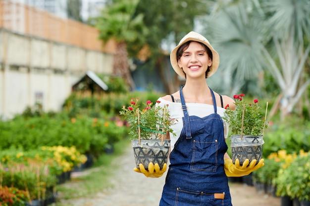 Jardineiro feliz mostrando flores desabrochando
