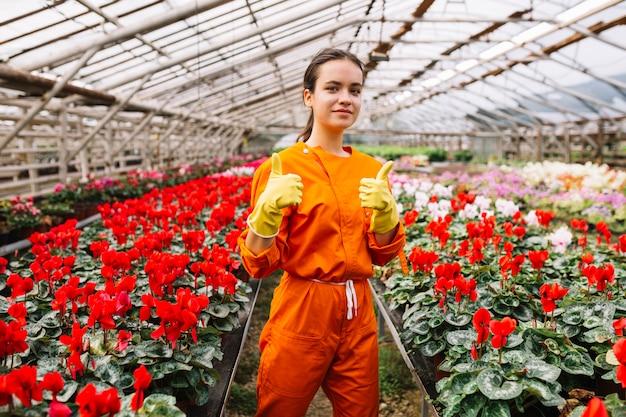 Jardineiro fêmea novo que gesticula os polegares acima com as flores frescas que crescem na estufa