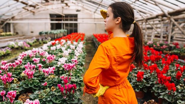 Jardineiro fêmea que protege seus olhos com as flores coloridas que crescem na estufa
