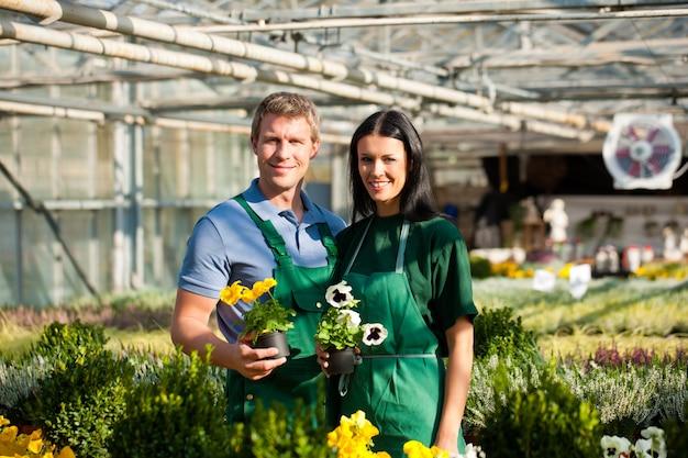 Jardineiro feminino e masculino no jardim do mercado