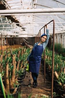 Jardineiro feminino em pé nas proximidades de vasos de plantas em estufa
