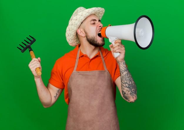 Jardineiro furioso com chapéu de jardinagem segurando o ancinho e gritando no alto-falante