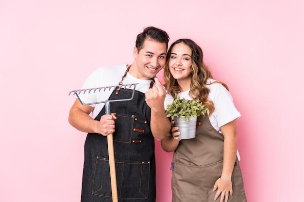 Jardineiro jovem casal apontando com o dedo para você, como se convidando se aproximar.