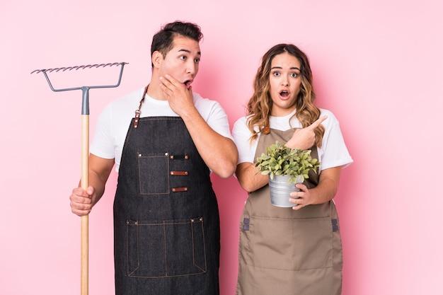 Jardineiro jovem casal isolado apontando para o lado