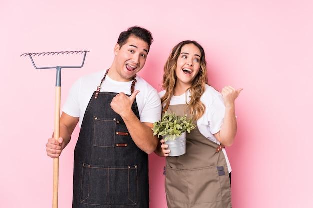 Jardineiro jovem casal isolado pontos com o dedo do polegar, rindo e despreocupado.