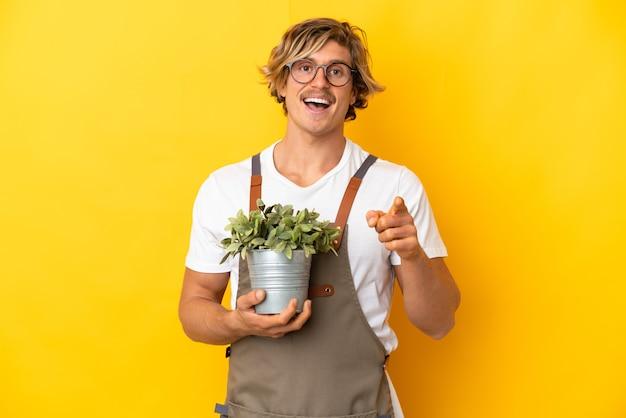 Jardineiro loiro segurando uma planta isolada