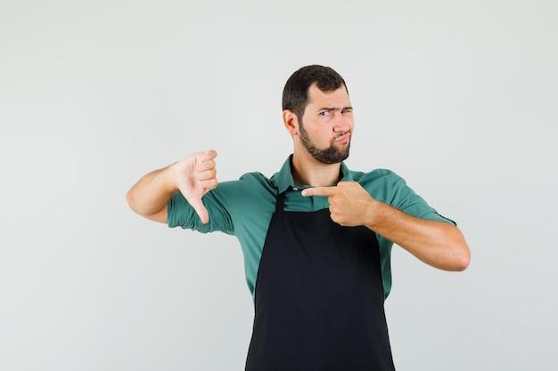 Jardineiro masculino apontando para o polegar para baixo em t-shirt, avental e parecendo desapontado. vista frontal.