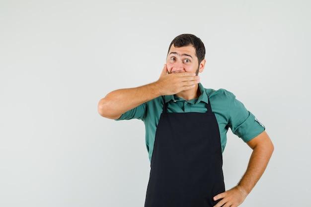 Jardineiro masculino cobrindo a boca com a mão na camiseta, avental e parecendo surpreso, vista frontal.
