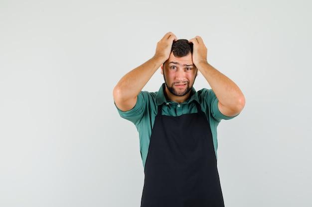 Jardineiro masculino de mãos dadas na cabeça em t-shirt, avental e olhando indefeso, vista frontal.