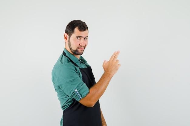 Jardineiro masculino em t-shirt, avental, mostrando gesto de tiro e olhando confiante, vista frontal.
