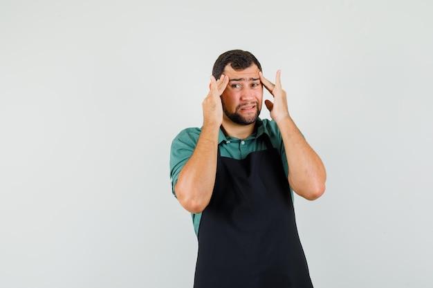 Jardineiro masculino em t-shirt, avental tendo forte dor de cabeça e parecendo doente, vista frontal.