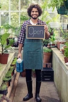 Jardineiro masculino, segurando o cartaz de sinal aberto e regador