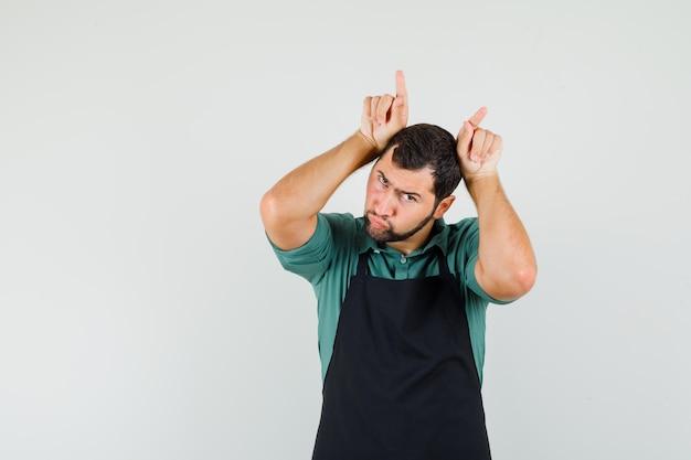 Jardineiro masculino segurando os dedos na cabeça como chifres de touro em t-shirt, avental e olhando engraçado, vista frontal.