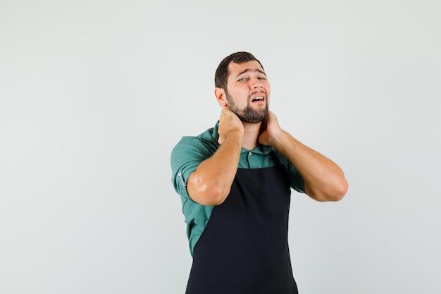Jardineiro masculino sofrendo de dor no pescoço em t-shirt, avental e parecendo exausto. vista frontal.