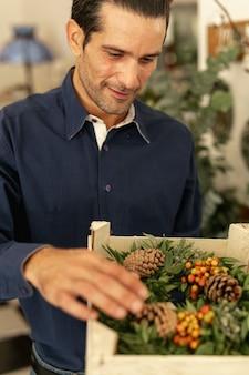 Jardineiro, olhando para grinaldas florais tiro médio
