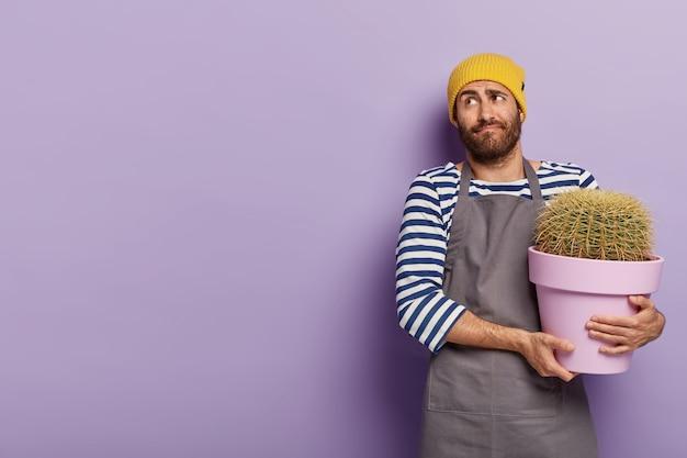 Jardineiro perplexo posando com um grande cacto em um vaso