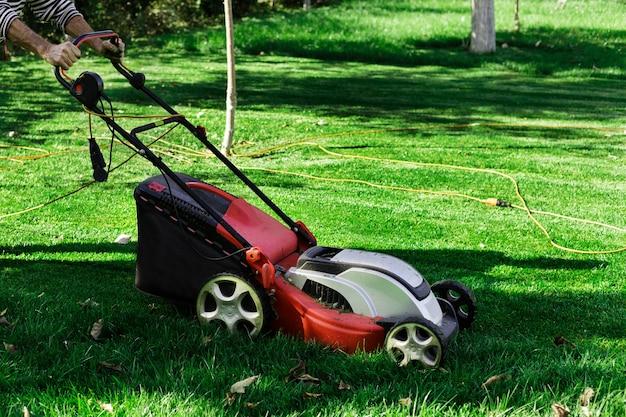 Jardineiro por cortador de grama elétrico cortando grama verde no jardim.
