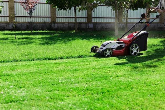 Jardineiro por cortador de grama elétrico, corte de grama verde no corte de gramado do prado do jardim. operário aparando grama no quintal