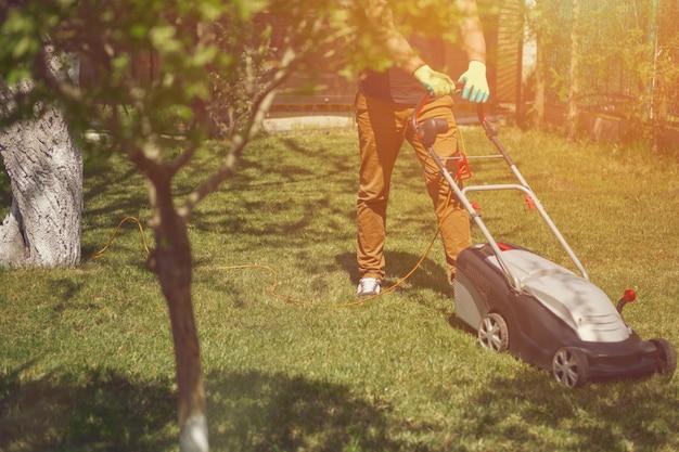 Jardineiro profissional com roupa casual e luvas está aparando a grama verde com um moderno cortador de grama.