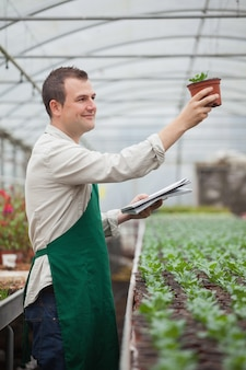 Jardineiro que olha alegremente as mudas enquanto toma notas