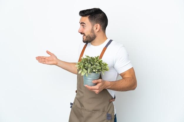 Jardineiro segurando uma planta isolada com expressão de surpresa enquanto olha de lado