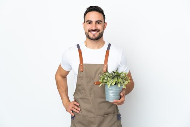 Jardineiro segurando uma planta isolada no fundo branco, posando com os braços na cintura e sorrindo