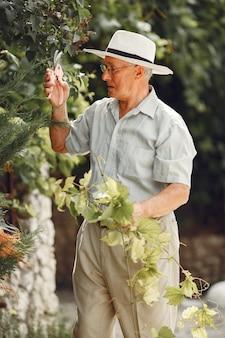 Jardineiro sênior está apreciando seu trabalho no jardim. velho com uma camisa branca.