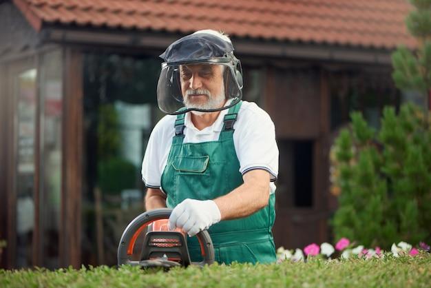Jardineiro usando proteção usando a máquina de aparar.
