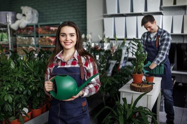Jardineiros com plantas em um belo centro de jardim