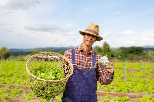 Jardineiros masculinos que têm vegetais e moeda de dólar em suas mãos.