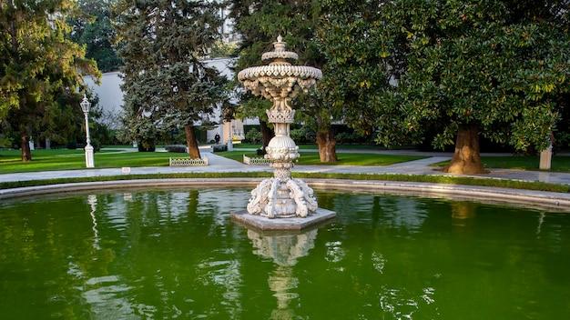 Jardins do palácio dolmabahçe com muito verde, fonte e lago com água, turquia