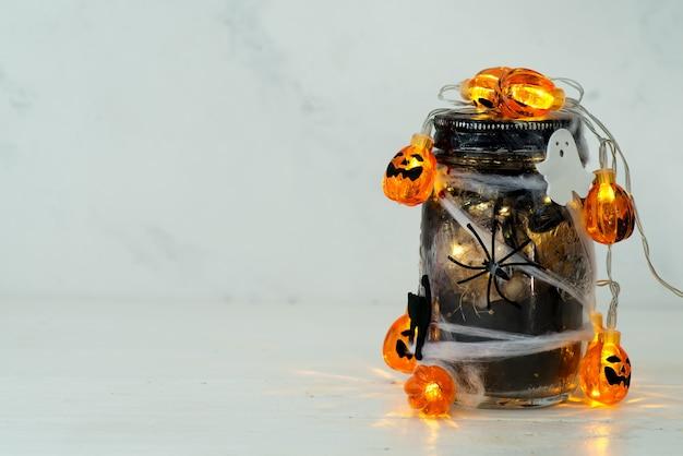 Jarra cheia de luzes cor de laranja na sala assustadora cheia de uma jarra preta com uma teia e uma aranha