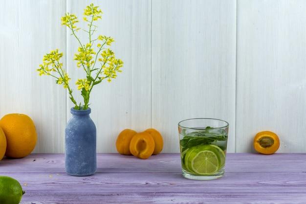 Jarra com flores amarelas de campo, damascos na mesa e um copo de mojito