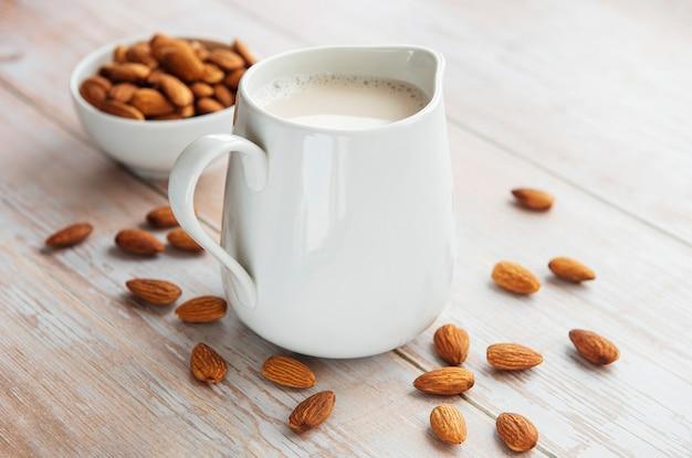 Jarra com leite de amêndoa e amêndoas na mesa