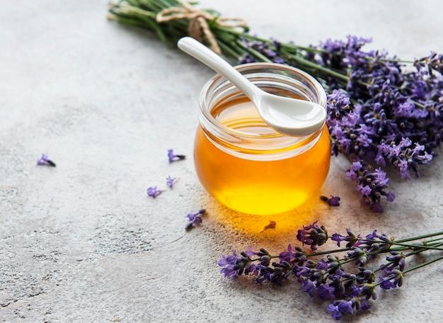 Jarra com mel e flores frescas de lavanda em um fundo de concreto