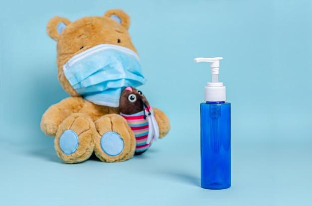Jarra com sabonete líquido, urso de pelúcia infantil, máscara médica protetora sobre uma superfície azul