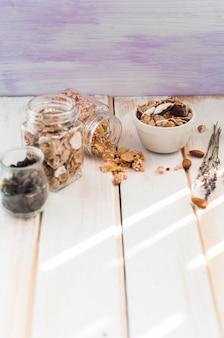 Jarra de granola; flocos de milho e lascas de chocolate perto de frutos secos na superfície de madeira