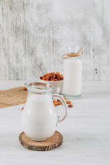 Jarra de leite com tigela de amêndoas e garrafa de leite, vista de alto ângulo em um fundo branco de madeira e pedaço de saco