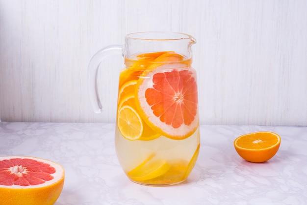 Jarra de limonada com laranja, limão e toranja na mesa Foto Premium