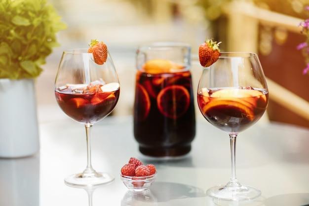 Jarra de sangria e copo com frutas