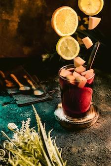 Jarra de sangria fria com frutas em uma superfície escura