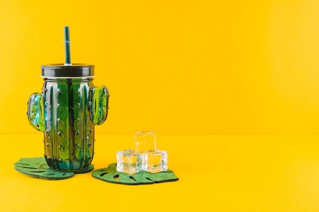 Jarra de suco de cacto de vidro e cubos de gelo de cristal nas montanhas russas de folhas contra pano de fundo amarelo